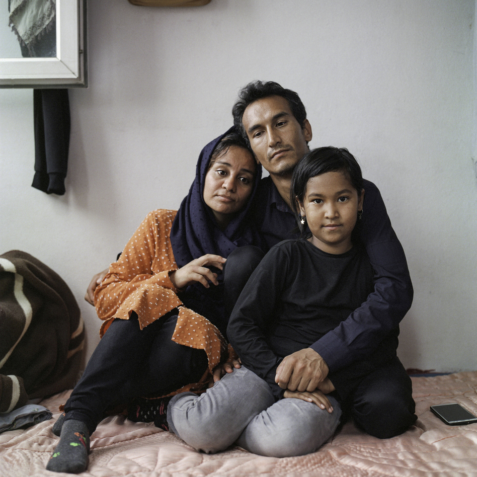 Sayyid Ali Hussaini (center), his wife Mahbube and daughter Elisa sit together in the Turkish city of Trabzon. Originally from the northern Afghan city of Mazar-e-Sharif, the family fled Taliban advances over the summer and arrived in Turkey last month. (Özge Sebzeci for NPR)