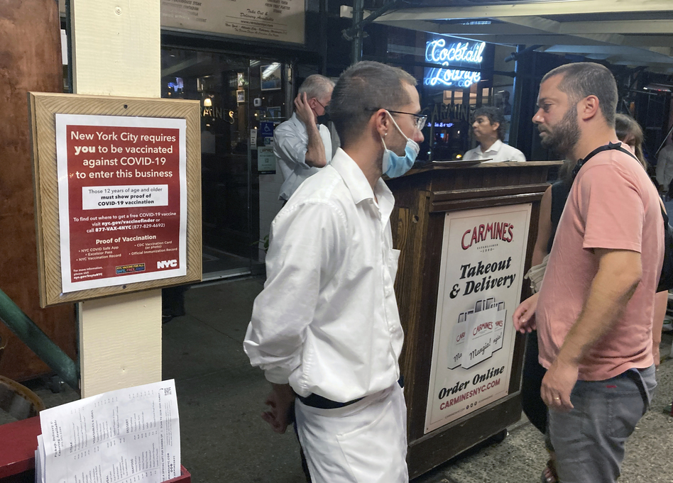 A sign in August informs customers that they must show proof of vaccination against COVID-19 in order to dine indoors at Carmine's Italian restaurant in Manhattan. (Ted Shaffrey/AP)