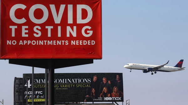 A Delta Air Lines plane lands near a COVID-19 testing sign at Los Angeles International Airport (LAX) on Aug. 25. Delta is increasing health insurance premiums for employees who are unvaccinated by $200 per month to cover higher costs of COVID-related care. The airline industry hasn't come out against a government-imposed vaccine mandate for domestic travel.