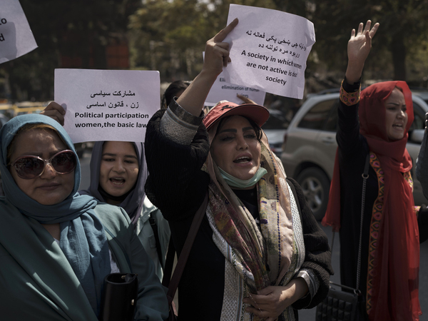 Women march to demand their rights under the Taliban rule during a demonstration near the former Women's Affairs Ministry building in Kabul, Afghanistan, on Sunday. The interim mayor of Afghanistan's capital said that many female city employees have been ordered to stay home by the country's new Taliban rulers.