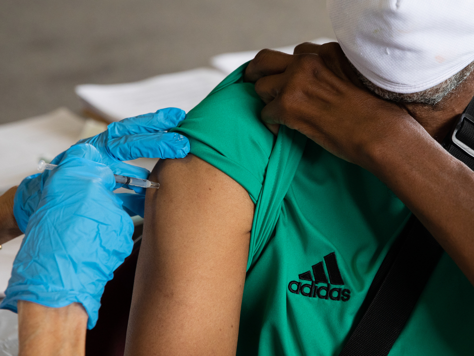 Rufus Peoples receives a dose of the Pfizer-BioNTech COVID-19 vaccine at a vaccination clinic in Southfield, Mich., in August. (Emily Elconin/Getty Images)