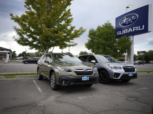 Two unsold 2021 Subaru SUVs sit in an otherwise empty storage lot at a Subaru dealership in Littleton, Colo., on Sept. 12. Ordering a car directly from an automaker can mean long waits, but doing so can be easier than finding a car you want at a dealer.