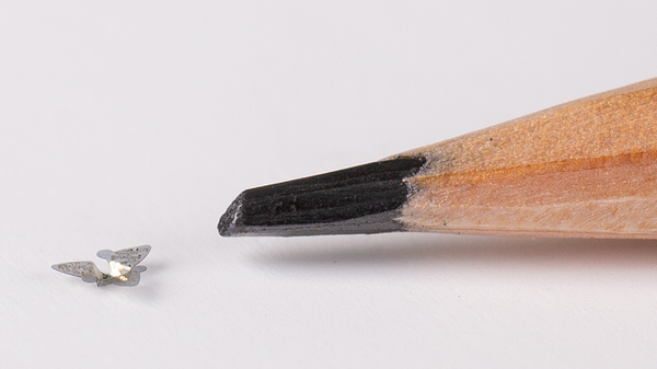A 3D microflier next to a pencil tip for scale.