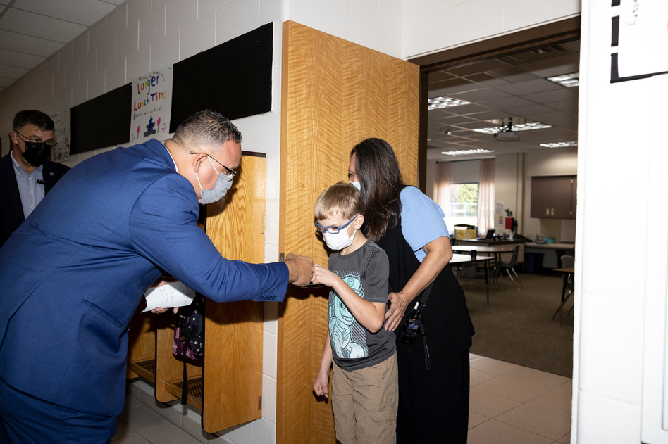 Cardona greets a student with a fist bump at Locust Lane Elementary School in Eau Claire.
