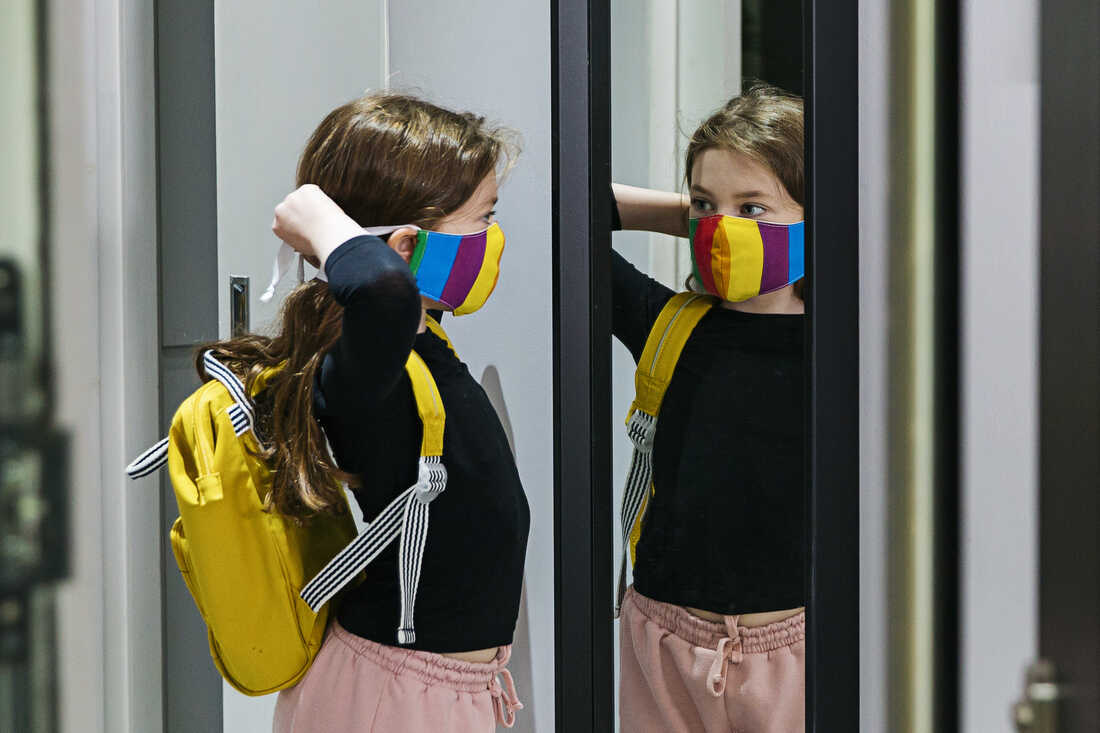 A young girl looks in the mirror as she puts on a colorful mask.