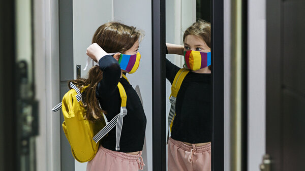 A girl with a backpack puts on a stripy mask.