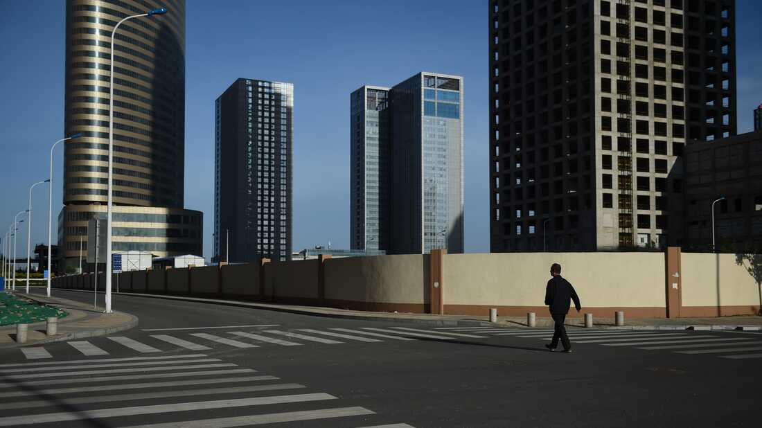 This photo taken on May 14, 2015 shows a man walking in an empty street in Conch Bay opposite the new Yujiapu financial district, in Tianjin, in northern China.