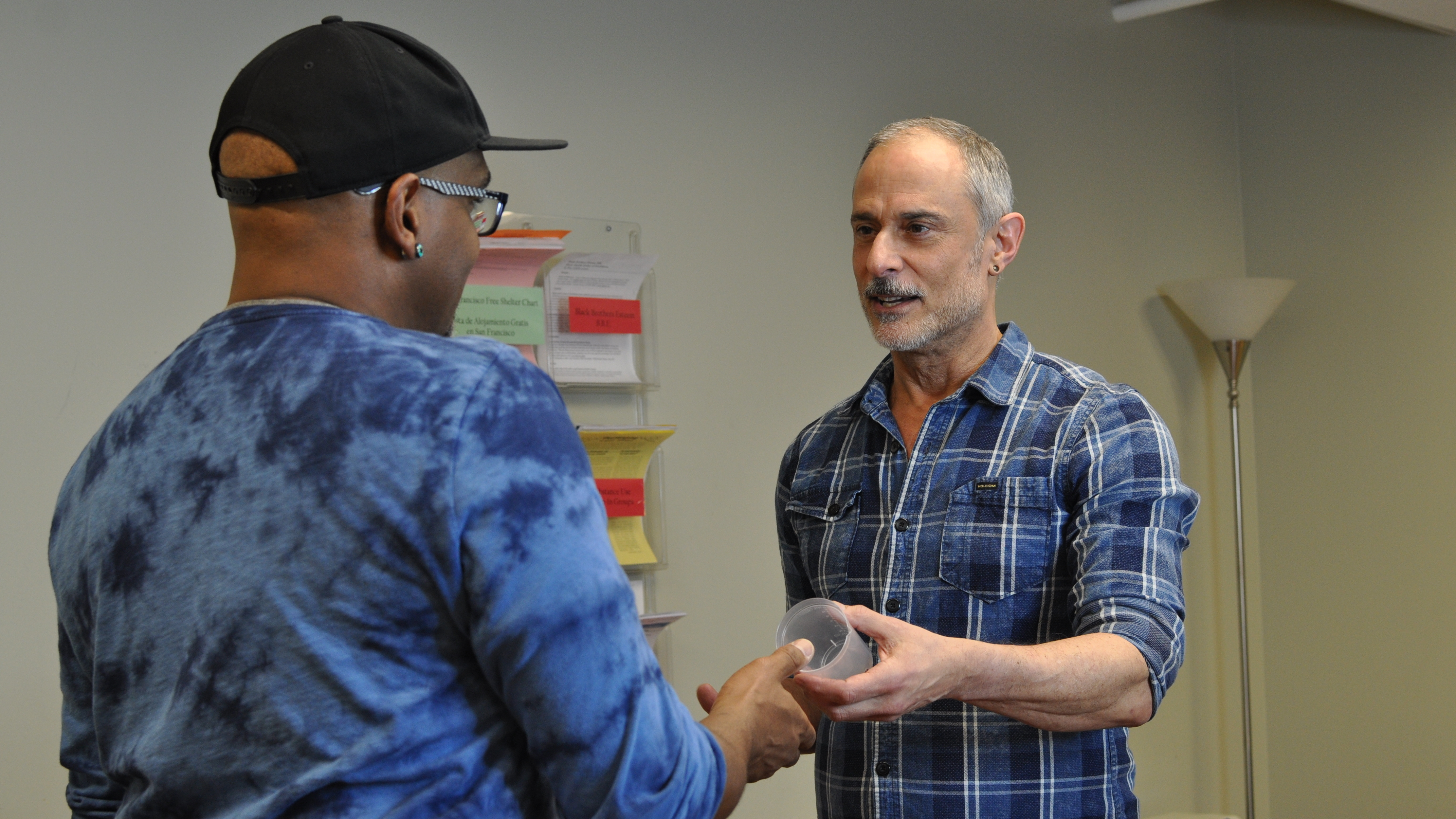 """At the San Francisco AIDS Foundation, staff members Tyrone Clifford (left) and Rick Andrews (right) demonstrate how a contingency management visit typically begins, with a participant picking up a specimen cup for a urine sample. If the sample tests negative for meth or cocaine use, the participant has an incentive dollar amount added to their """"bank"""" which can later be traded for a gift card."""