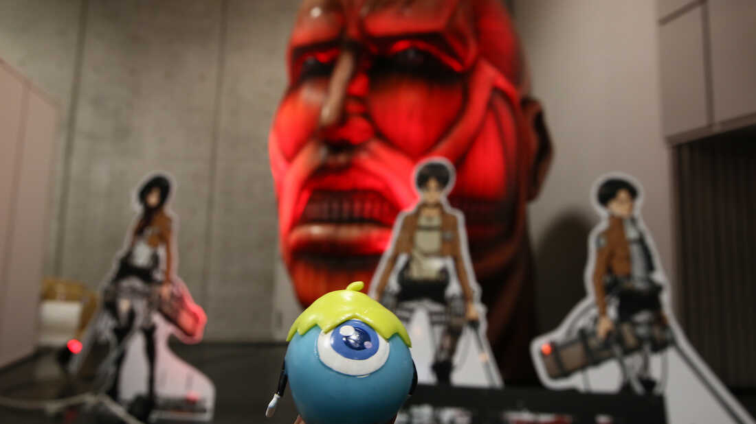 Mascot Su on display in front of Attack on Titan figures.