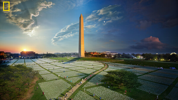 """A composite photograph captures the passage of day to night at the """"In America: Remember"""" art installation on the National Mall in Washington, D.C. Each flag represents an American life lost to COVID-19."""
