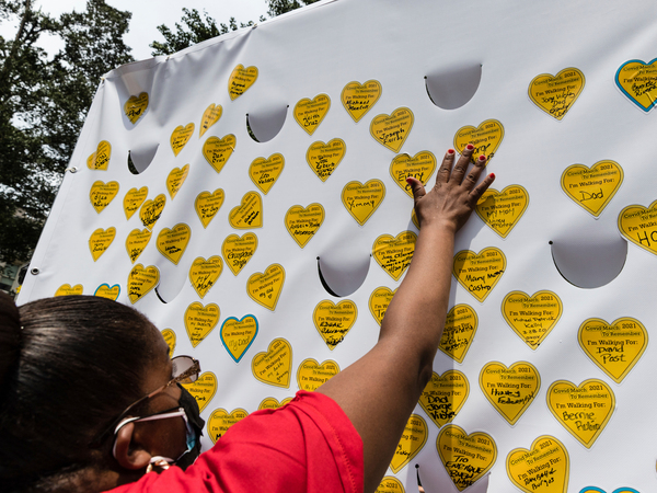 COVID-19 survivors gather in New York and place stickers representing lost relatives on a wall, in remembrance of those who've died during the pandemic.