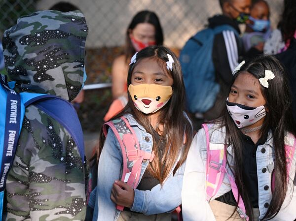 Students and parents arrive masked for the first day of the school year at Grant Elementary School in Los Angeles on Aug. 16. The reopening of schools has raised hope that some parents may return to the labor force.