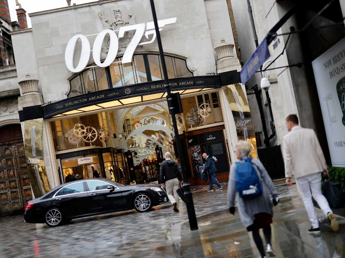 """A pedestrian walks past a James Bond 007 logo above the entrance to Burlington Arcade in London on October 4, 2021, following the release of the latest James Bond film """"No Time To Die"""" . (Photo by Tolga Akmen / AFP) (Photo by TOLGA AKMEN/AFP via Getty Images)"""