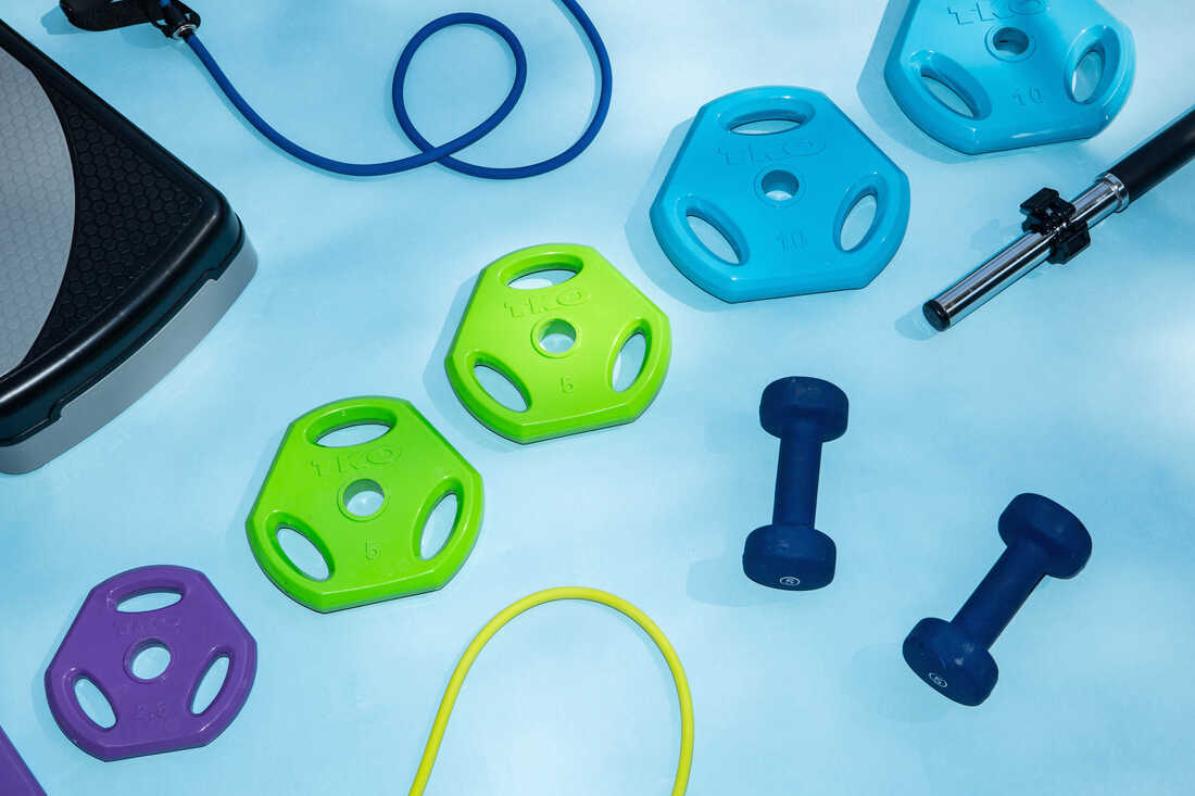 Colorful weights are laid out on a light blue background. There are 5-pound hand weights, and weights that go on a barbell. There are also exercise bands and a bench.