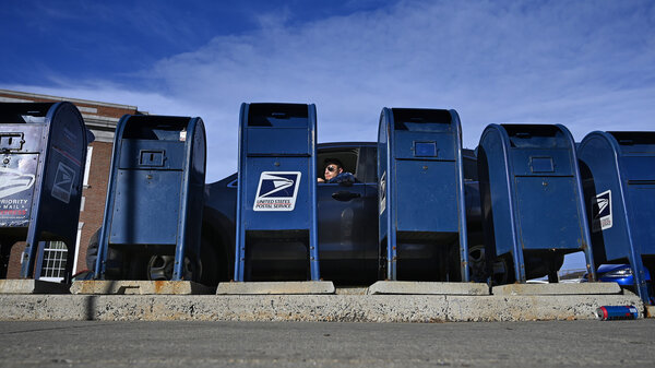A man pulls up to drop off mail at the mailboxes at the Portland Post Office in Portland, Maine, on Dec. 4, 2020.