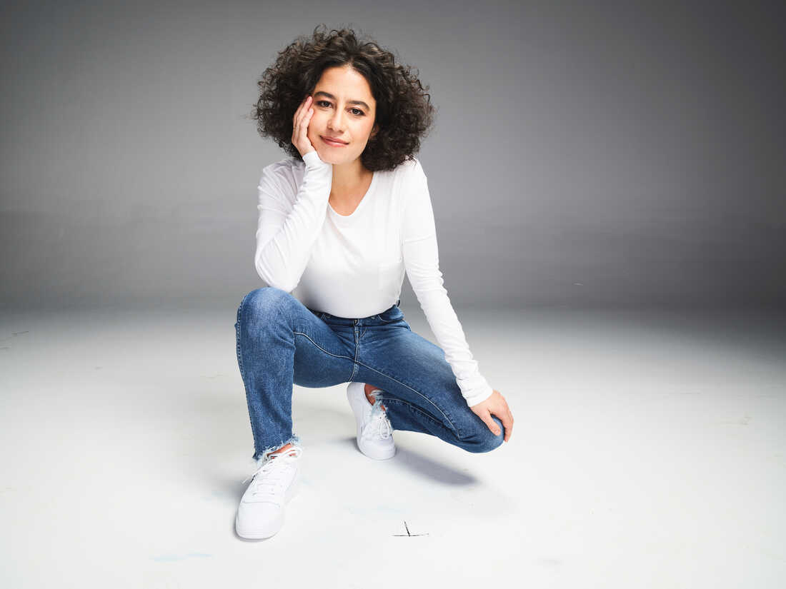 Ilana Glazer kneels in a white shirt and blue jeans