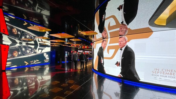 Advertisements in a theater in London's Leicester Square show Daniel Craig as James Bond in No Time to Die. Ahead of its opening in the U.S. this weekend, the film had taken in more than $120 million in 54 foreign markets.
