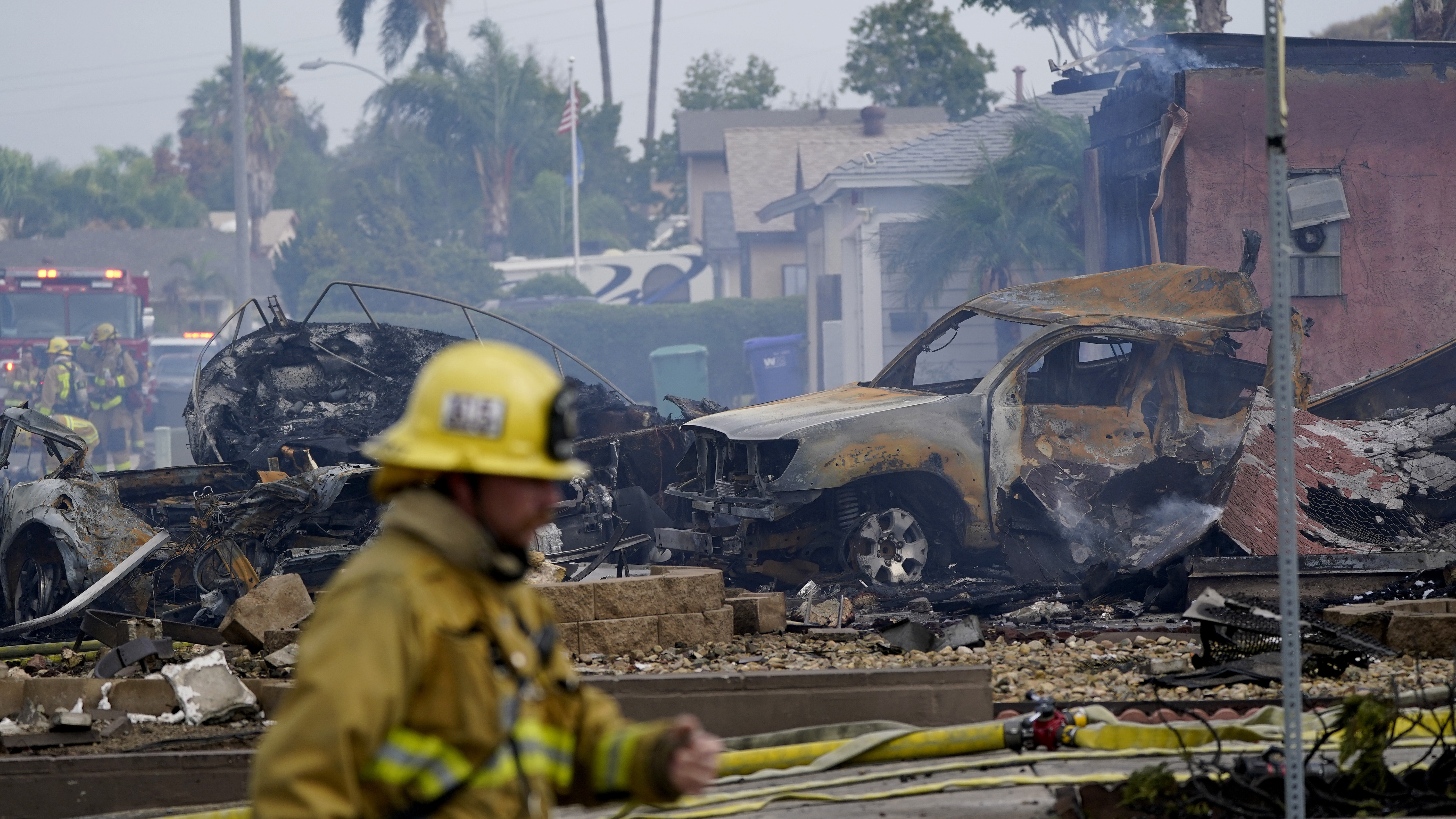 Fire crews work the scene of a small plane crash on Monday in Santee, Calif. At least two people were killed and two others were injured when the plane crashed into the suburban neighborhood, setting two homes ablaze.