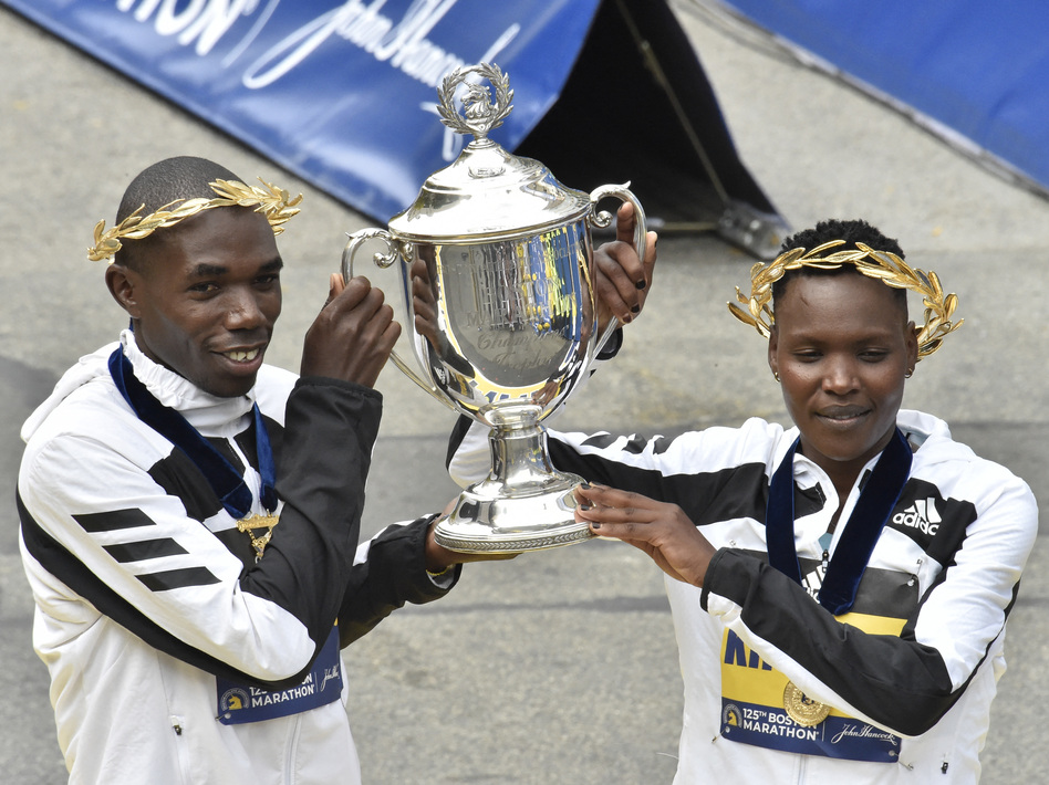 Benson Kipruto (L) and Diana Kipyogei (R) of Kenya hold up the victory trophy after taking first place in the professional men's and women's divisions during the 125th Boston Marathon in Boston, Massachusetts on Monday. The first Boston Marathon since April 2019 strayed from tradition in several ways. (Joseph Prezioso/AFP via Getty Images)