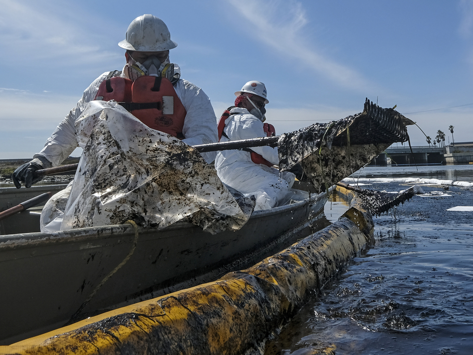 Cleanup contractors deploy skimmers and floating barriers known as booms to try to stop further crude oil incursion into Talbert Marsh in Huntington Beach, Calif., on Oct. 3 after an oil spill off the Southern California coast. (Ringo H.W. Chiu/AP)