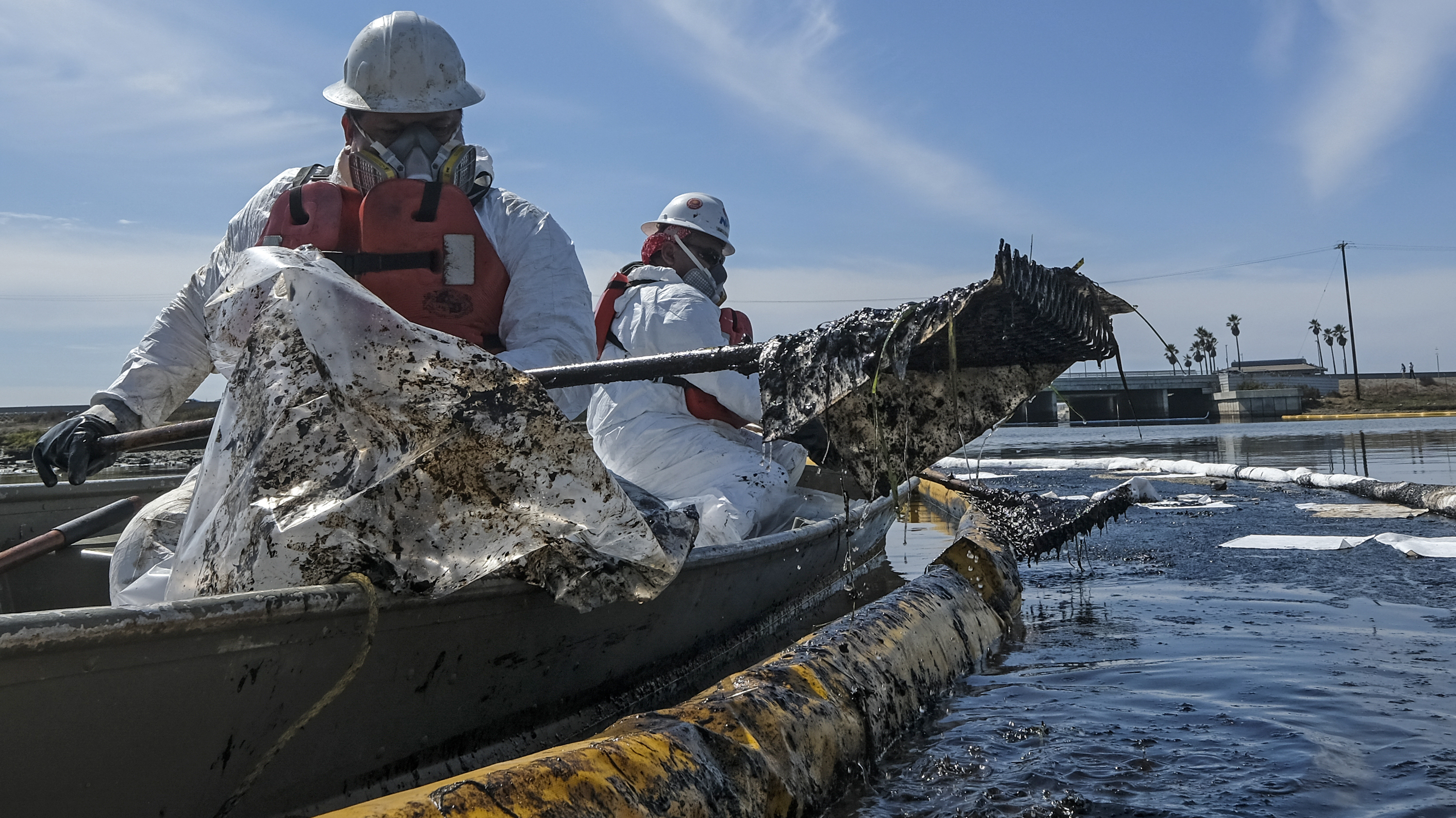 Cleanup contractors deploy skimmers and floating barriers known as booms to try to stop further crude oil incursion into Talbert Marsh in Huntington Beach, Calif., on Oct. 3 after an oil spill off the Southern California coast.