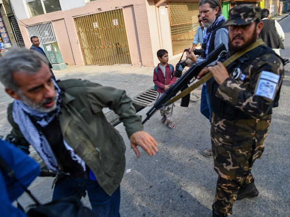 A member of the Taliban special forces pushes a journalist covering a demonstration by women protesters in Kabul on Sept. 30.