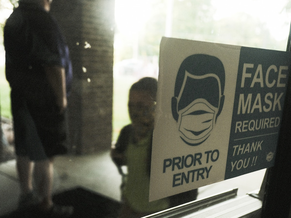 In federal lawsuits, parents in Wisconsin are blaming school districts for COVID-19 infections, saying they should not have ended mask requirements during a pandemic. Here, a student in Michigan is seen arriving at school in late August.