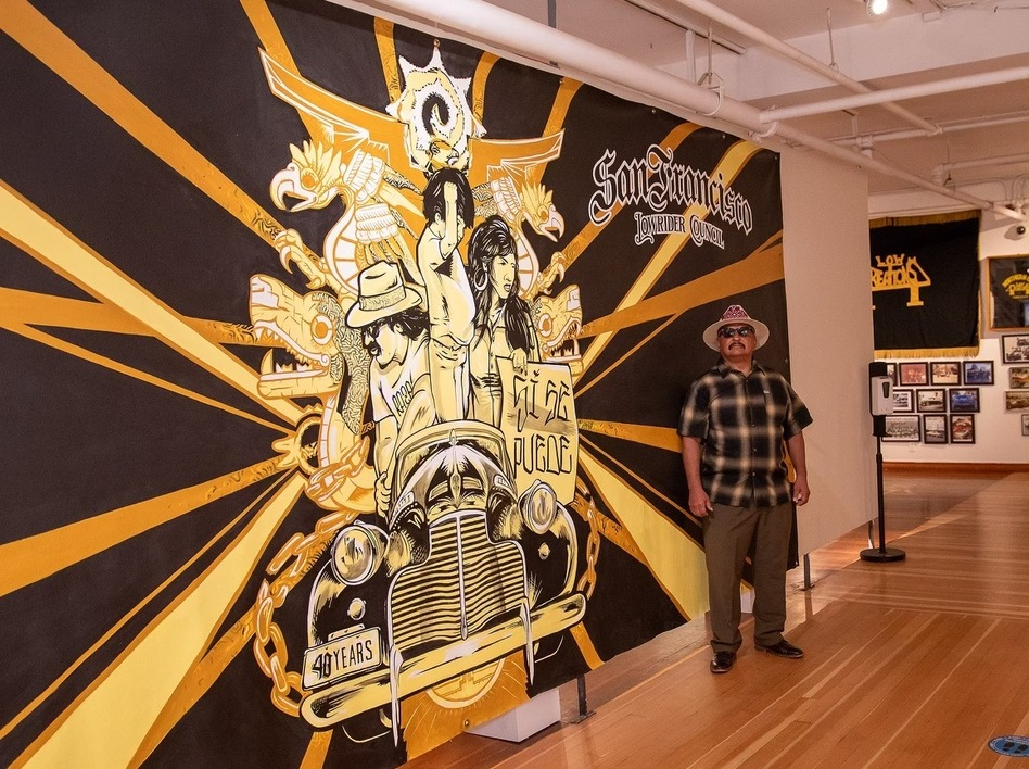 Roberto Y. Hernandez, founder and president of the San Francisco Lowrider Council, stands at the entrance to an exhibit about the council at the Mission Cultural Center for Latino Arts.