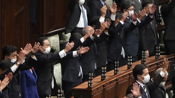Japanese Prime Minister Fumio Kishida, forth from left, and other lawmakers give three cheers after dissolving the lower house, the more powerful of the two parliamentary chambers, during an extraordinary Diet session at the lower house of parliament Thursday.