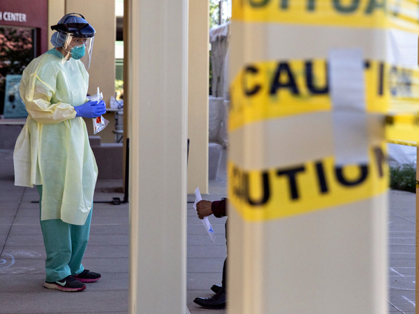 A doctor stands at a walk-up coronavirus testing site at West County Health Center in San Pablo, Calif. in April 2020. Pandemic burnout has effected thousands of health care workers.