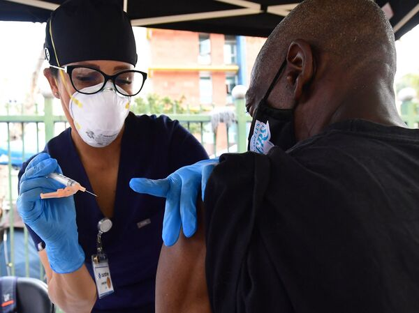 Nurse Christina Garibay administers Johnson & Johnson's COVID-19 vaccine to a man at a community outreach event in Los Angeles in August.