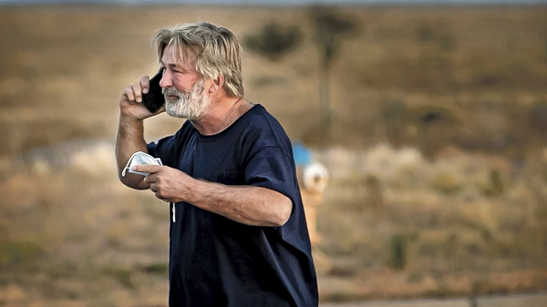 Alec Baldwin speaks on the phone in the parking lot outside the Santa Fe County Sheriff
