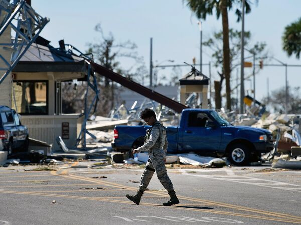 A military police officer walks near a destroyed gate in Tyndall Air Force Base in Florida in the aftermath of Hurricane Michael on Oct. 12, 2018. The Pentagon says climate change is a national security concern.
