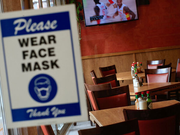 A sign asking patrons to wear a mask is seen at the entrance of a restaurant in New York City on Aug. 3. The spread of the delta variant is expected to have led to sharply slower economic growth in the July-to-September quarter.