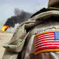 A U.S. soldier stands near an oil well set ablaze by retreating Iraqi troops.