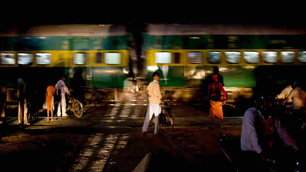 Just outside Noida at a railroad crossing, a bicyclist waits inches away from the train to continue