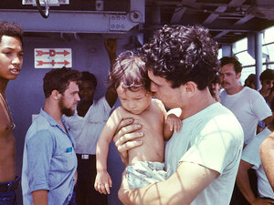 A USS Kirk crewmember tends to a Vietnamese baby.