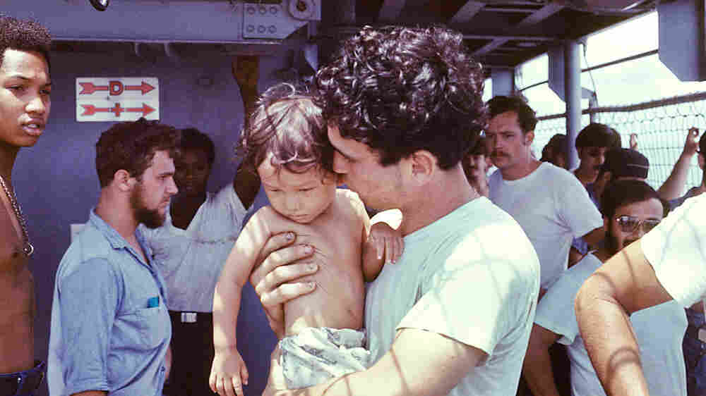 A USS Kirk crew member tends to a Vietnamese baby.