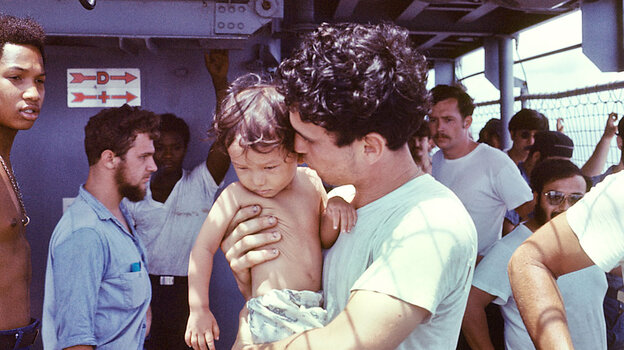 A USS Kirk crew member tends to a Vietnamese baby.