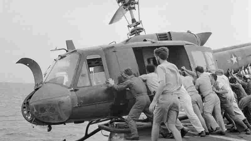 Crew members push a Huey into the ocean to make room for more helicopters full of refugees.