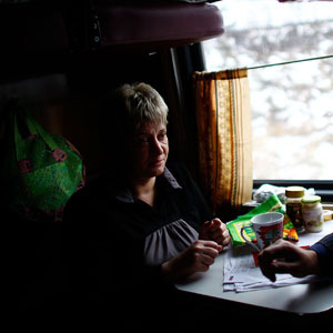 Zhanna Rutskaya (left) and Sergei Yovlev share food on the train, which is traveling to the Russian city of Yaroslavl, about four hours northeast of Moscow. (David Gilkey/NPR)