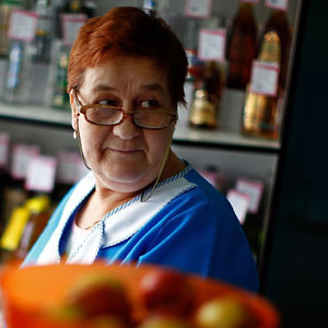 Tatiana Ilyinichna works behind the counter of a small grocery store. (David Gilkey/NPR)