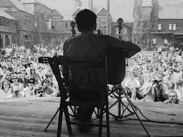 Bob Dylan on stage at the tennis courts in Newport; credit: Rowland Scherman.