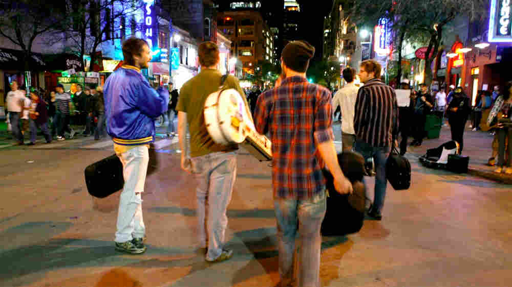 A band lugs their gear down 6th Street in Austin during SXSW.