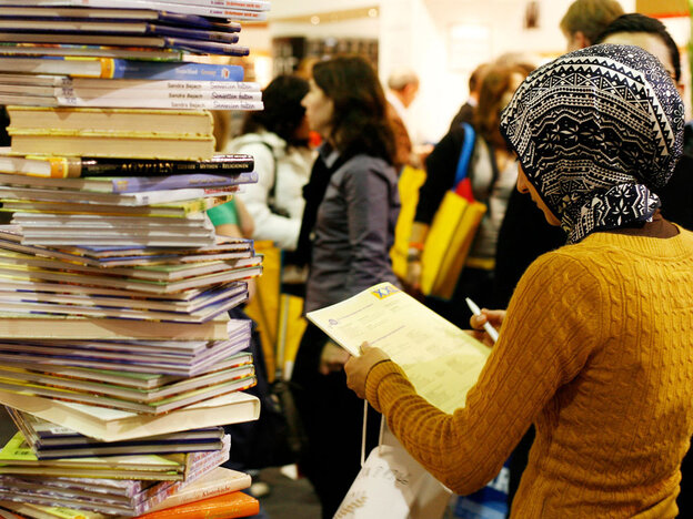 Woman in front of a stack of books; credit: Sebastian Willnow / AFP / Getty Images