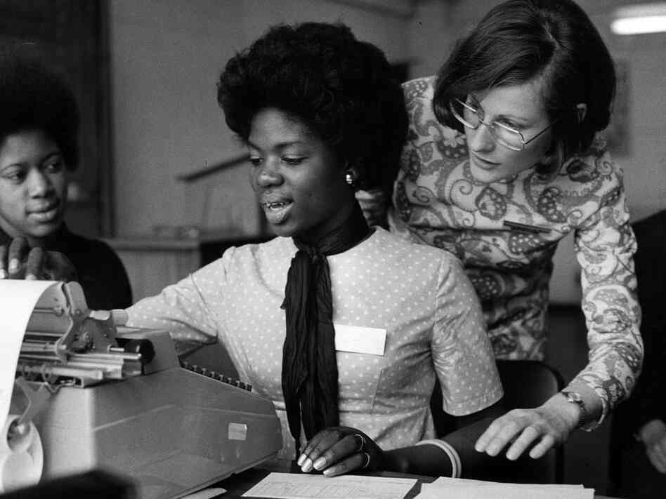Women around a typewriter; Erich Auerbach/Getty Images