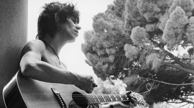 A young Keith Richards, barechested and with an acoustic guitar.