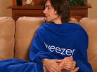 Weezer's Brian Bell rubs someone's feet in a Snuggie.