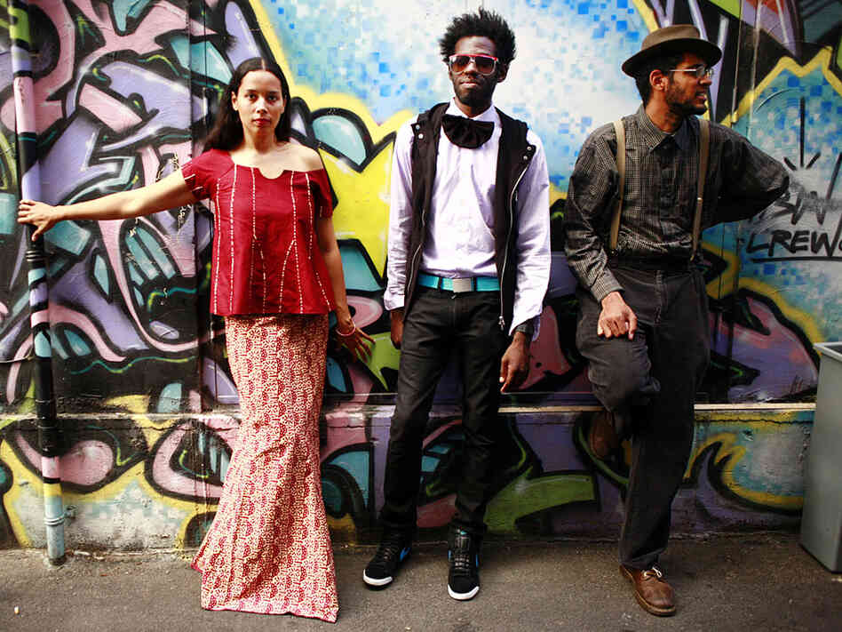 The three members of Carolina Chocolate Drops stand in front of a mural