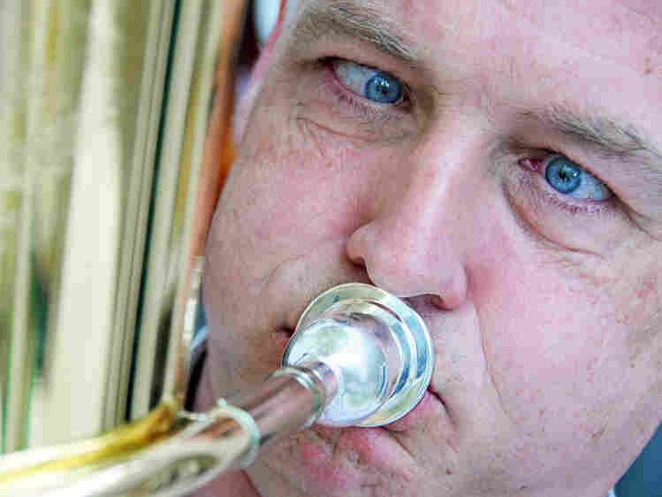 A man blows into a brass instrument